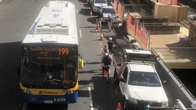 Pedestrians walking between parked vehicles and a bus on Adelaide Street.