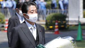 Japanese Prime Minister Shinzo Abe carries a bouquet of flowers at a ceremony marking 75 years since the end of the war, on August 15.