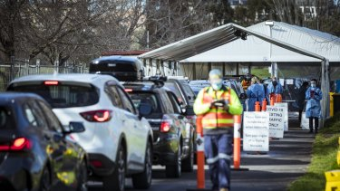 Long lines of people wait to get their COVID-19 test at Albert Park in Melbourne.
