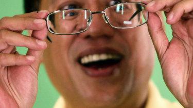 Then still a candidate, Benigno Aquino checks his glasses prior to a live television interview in 2010.