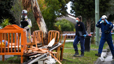 Police and Arson Squad detectives at the scene of a fatal house fire in Dandenong on Sunday night.
