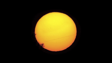 Mercury is seen as a small silhouette, centre left, as it travels across the face of the sun, near capital Nicosia, Cyprus.
