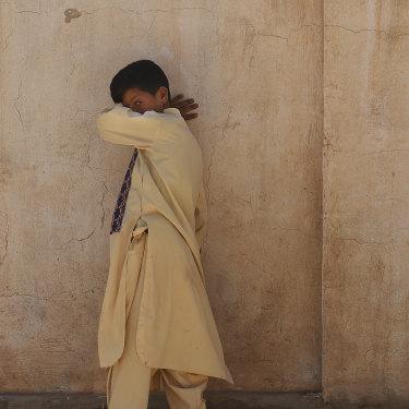 A boy walks along a wall at Zero Point.