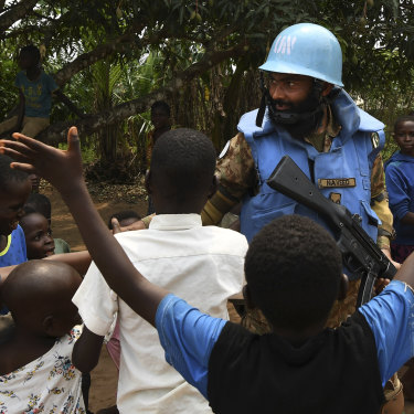 A United Nations peace keeper from Pakistan shakes hands with children while on patrol in a village near Kananga in Kasai Central.