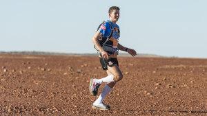 Kay Bretz running on gibber plains on day two of the Big Red Run, a 250-kilometre race through the Simpson Desert.