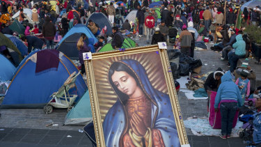 A pilgrim carries on his back a framed image of the Virgin of Guadalupe at the Basilica of Guadalupe in Mexico City.