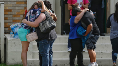Parents and students embrace outside a gym where students had waited to be reunited with their families.