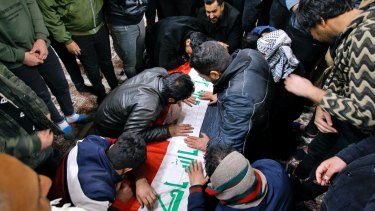 People mourn by the flag-draped coffin of a suicide bomb victim, Samer Hassan during his funeral procession at the Imam Ali shrine in Najaf, Iraq.