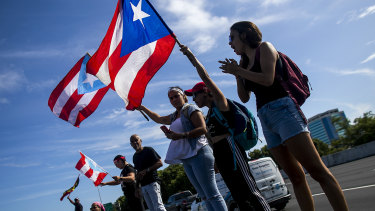 Demonstrators wave Puerto Rican flags during a protest in San Juan, Puerto Rico.