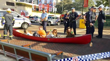 Firefighters prepare to cut the activists from their canoe on the footpath next to Stanley Street.