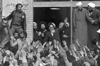 The Ayatollah Ruhollah Khomeini waves to followers from the balcony of his headquarters in Tehran in 1979.