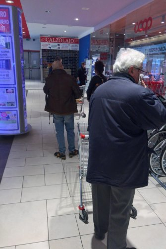 People in line for a supermarket in Alessandria. Only 10 people are allowed in at a time and must stand 1.5 metres apart while waiting in line.