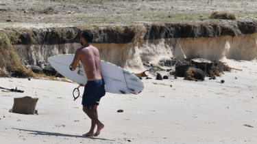 A surfer walks near beach erosion at Kirra on the Gold Coast on Saturday.