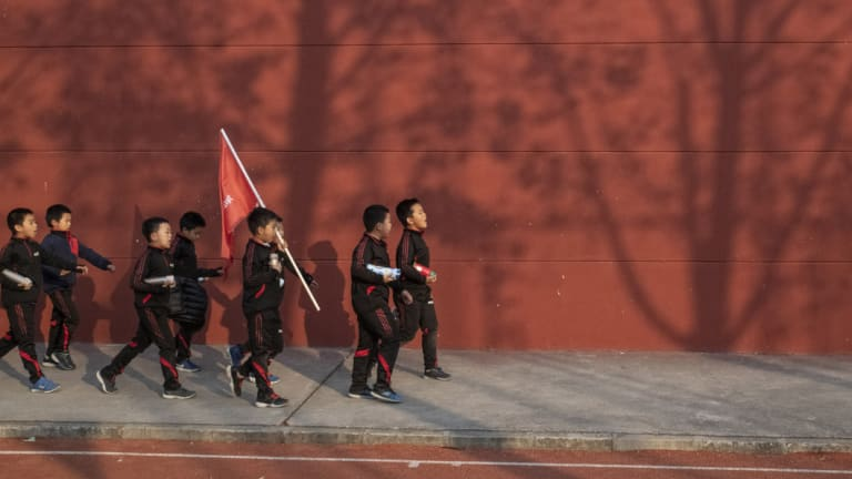 Backbone of the Chinese people: The Real Boys Club walk to their bus at the end of training.