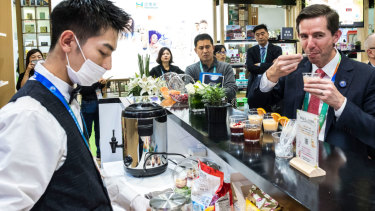 Trade Minister Simon Birmingham trying vitamin drinks at the Swisse stand on day one of the China International Import Expo in Shanghai this week.