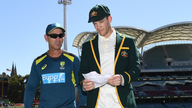 Long day ahead: Australian coach Justin Langer walks from the field with Tim Paine after losing the toss in Adelaide.