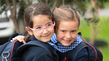 Brunswick prep students Eleni (left) and Zara embrace as they return to school on Monday morning after 74 days of remote learning.