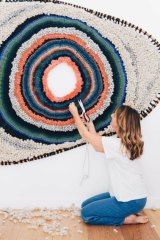 Textile artist Tammy Kanat with one of her woven abstract wall-hangings.