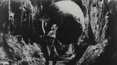 Indiana Jones (Harrison Ford) runs for his life as a huge boulder threatens to crush him in Raiders of The Lost Ark.