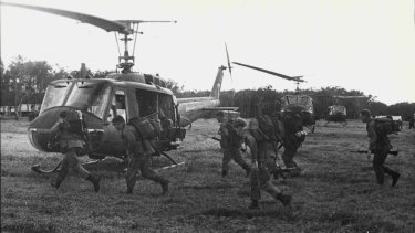 Troops of the 3rd Battalion, Royal Australian Regiment, run to board helicopters on the flyout from Kapyong Pad.