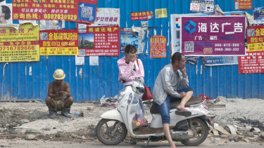 People wait in front of advertisements in Chinese pasted on a fence outside a construction site in Sihanoukville, Cambodia.
