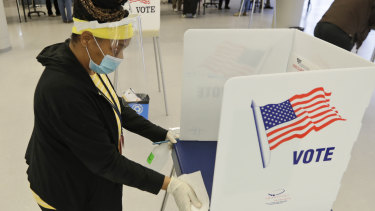 A worker cleans an election booth after a person voted at the Cuyahoga County Board of Elections in Cleveland.