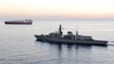 HMS Montrose accompanies a commercial ship through the narrow Strait of Hormuz.