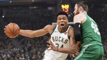 Bucks superstar Giannis Antetokounmpo drives past Australian Aron Baynes.