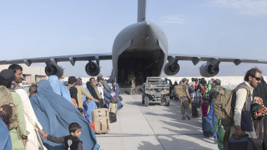 People wait in line to board a US Air Force plane in Kabul.