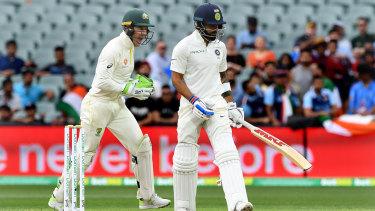 Australian captain Tim Paine celebrates as Indian captain Virat Kohli leaves the field after being dismissed by Australian bowler Nathan Lyon for 34 runs.
