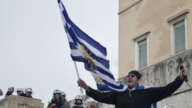 A Greek Orthodox monk waves a Greek flag during a protest against the agreement between Greece and Macedonia over dispute of the former Yugoslav's republic name, outside the Greek Parliament, in Athens, Saturday.