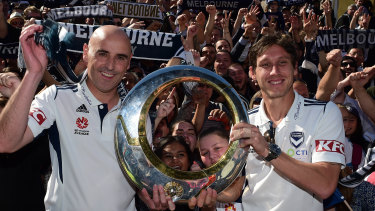 Coach Kevin Muscat and then-skipper Mark Milligan toast Melbourne Victory's 2015 A-League championship with fans following their 3-0 grand final win against Sydney FC.