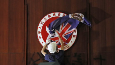 A protester covers the Hong Kong emblem with the Hong Kong colonial flag in the Legislative Council chambers during protests on Monday.