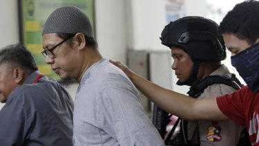 Zainal Anshori, leader of Jemaah Anshorut Daulah, is escorted by police officers at South Jakarta District Court on Tuesday.