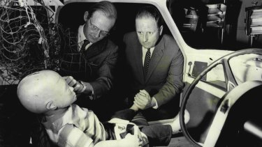 Dr Michael Henderson (left), head of the Traffic Accident Research Unit, shows  Milton Morris a special child dummy after a simulated accident in 1972.