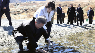 South Korean President Moon Jae-in puts water from the crater lake into a bottle as his wife Kim Jung-sook watches.