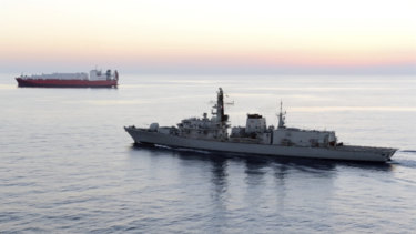 A file photo of the HMS Montrose accompanying a commercial ship through the narrow Strait of Hormuz.