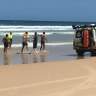 The two men are helped from the water at Fraser Island on Wednesday.