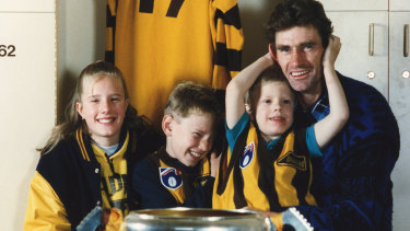 Shane Tuck between siblings Renee and Travis with their father, Hawks great Michael Tuck, in 1991.