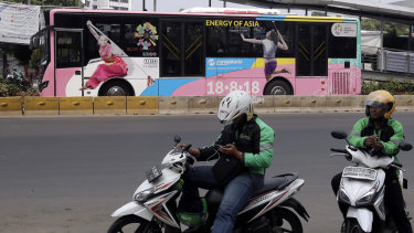 Motorcycle taxi drivers wait for customers as a bus with Asian Games promotional stickers drives past in Jakarta.
