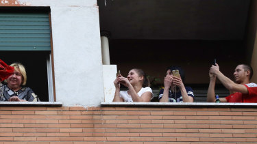 People stand at the window of their apartments during lockdown in Italy.