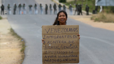 A Venezuelan holds a sign that reads in Spanish:  Venezuelan migrants at the border between Brazil-Venezuela, we support the humanitarian aid. Maduro assassin.