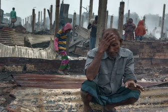 A Rohingya refugee sits by charred remains after the fire in Nayapara Camp in Cox's Bazar.