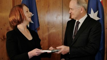 Ross Garnaut presents Julia Gillard with his climate change report in 2011.