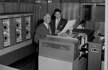 Mr. K. Thomas, chairman of Thomas Nationwide Transport Ltd. (left) and Mr. Barry Z. de Ferranti N.S.W. manager I.C.T. at the official switch-on of the 1902 computer at TNT's Mascot terminal. April 14, 1966.