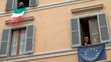 Italian and European Union flags hang from windows in a  Rome street.
