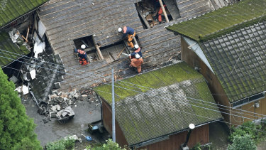 Rescuers work on the rooftop of the house damaged by a landslide in Soo, Kagoshima prefecture, western Japan, on July 4 last year.