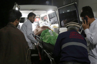 A wounded man is carried to a hospital after the explosion ripped through a wedding hall on a busy Saturday night in Afghanistan's capital.