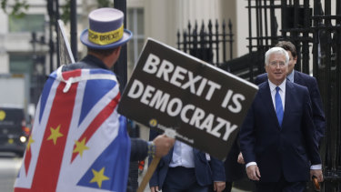 Britain's Conservative MP Michael Fallon passes a demonstrator near the launch of Boris Johnson's leadership campaign in London last week.
