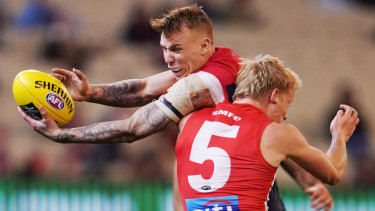 Isaac Heeney of the Swans tackles James Harmes of the Demons.